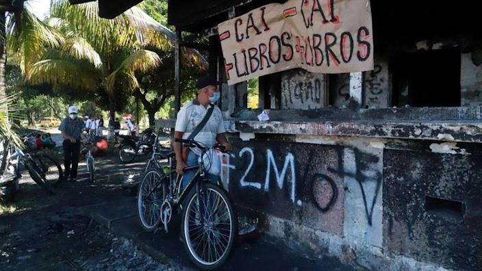 A man is protesting police atrocities in a recent protest against President Ivan Duque's government tax reform in Cali, Colombia, on May 3, 2021. I'm looking at the police station that burned down.