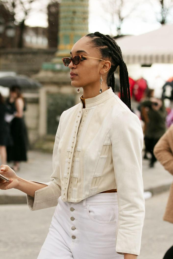 """Indira Scott hit the streets of Paris <a href=""""https://www.refinery29.com/en-us/2019/04/227900/indira-scott-model-box-braids-makeup-interview"""" rel=""""nofollow noopener"""" target=""""_blank"""" data-ylk=""""slk:with her trademark braids"""" class=""""link rapid-noclick-resp"""">with her trademark braids</a> pulled back into pigtails. <span class=""""copyright"""">Photographed by Hannan Saleh.</span>"""