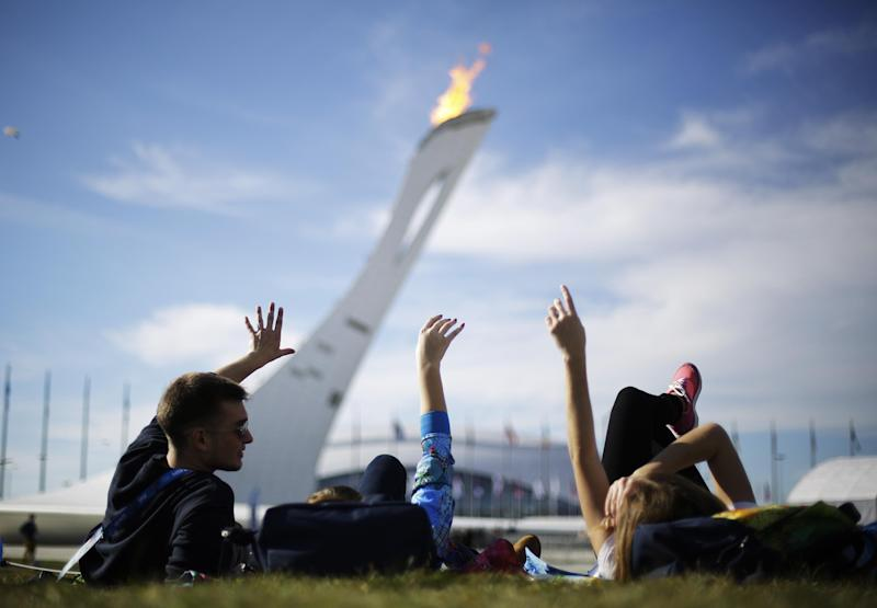 In this Wednesday, Feb. 12, 2014, photo, volunteers from left, Vladimir Malakhov, Elena Ripenko, and Aleksandra Zhuk, lay out on the lawn under the Olympic cauldron at the 2014 Winter Olympics, in Sochi, Russia. Temperatures were near 60 degrees Fahrenheit in Sochi on Wednesday. (AP Photo/David Goldman)