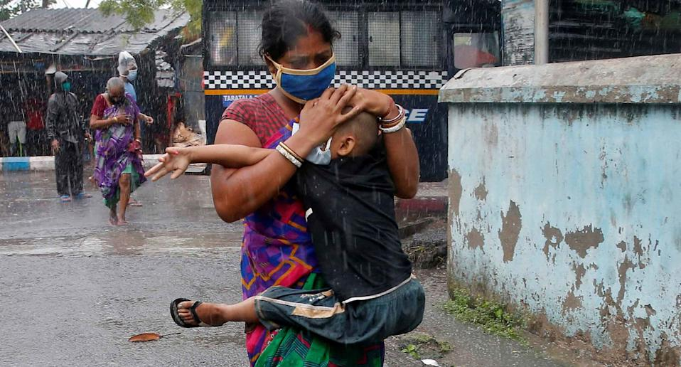 A woman shown clutching her child in heavy rain as they evacuate a slum in Kolkata. Source: Reuters