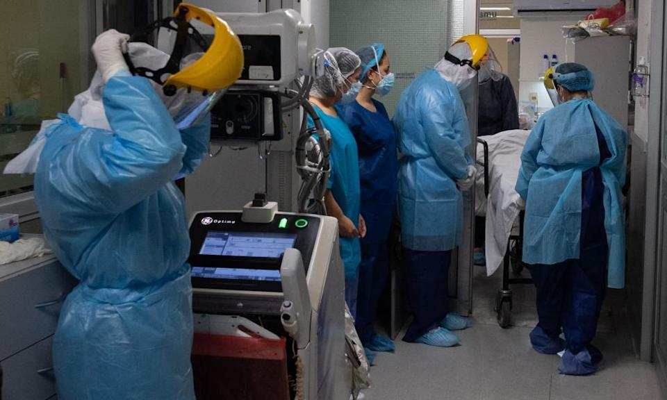 Morgue workers remove the body of a patient who died of Covid-19 at a private hospital in Montevideo, Uruguay.