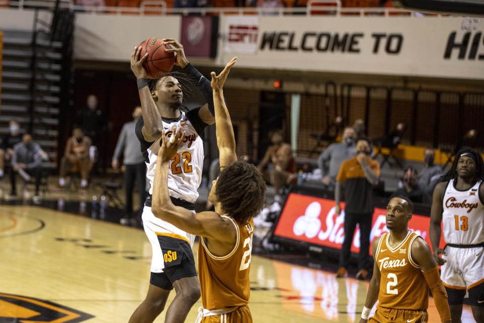 Oklahoma State forward Kalib Boone (22) shoots the ball over Texas forward Jericho Sims (20) during the first overtime of the NCAA college basketball game in Stillwater, Okla., Saturday, Feb. 6, 2021. (AP Photo/Mitch Alcala)