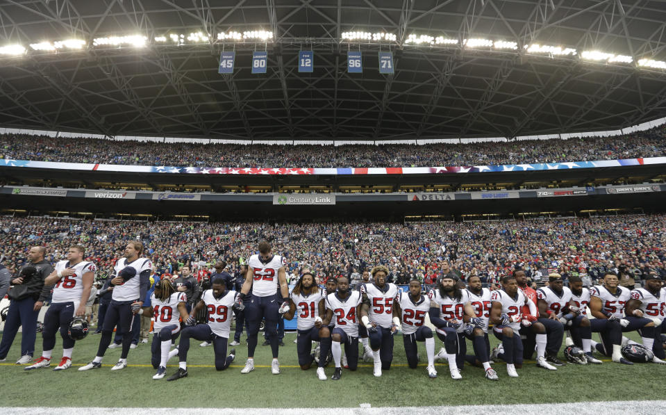 """FILE - In this Oct. 29, 2017, file photo, Houston Texans players kneel and stand during the singing of the national anthem before an NFL football game against the Seattle Seahawks, in Seattle. NFL owners have approved a new policy aimed at addressing the firestorm over national anthem protests, permitting players to stay in the locker room during the """"The Star-Spangled Banner"""" but requiring them to stand if they come to the field. The decision was announced Wednesday, May 23, 2018, by NFL Commissioner Roger Goodell during the league's spring meeting in Atlanta. (AP Photo/Elaine Thompson, File)"""