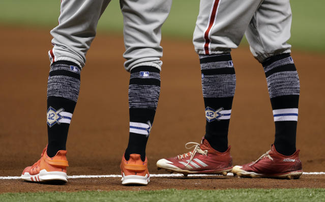 Philadelphia Phillies' Scott Kingery, right, and first base coach Jose David Flores wear socks with the number 42 on them honoring the memory of Jackie Robinson during the fifth inning of a baseball game against the Tampa Bay Rays Sunday, April 15, 2018, in St. Petersburg, Fla. (AP Photo/Chris O'Meara)