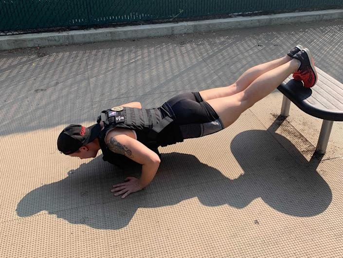 a sweaty fitness reporter doing decline push-ups in a weight vest