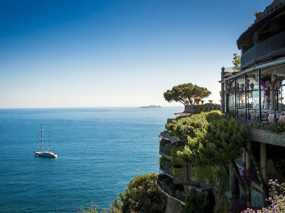"""Once <a href=""""https://www.cntraveler.com/story/a-guide-to-positanos-quiet-side?mbid=synd_yahoo_rss"""" rel=""""nofollow noopener"""" target=""""_blank"""" data-ylk=""""slk:Positano"""" class=""""link rapid-noclick-resp"""">Positano</a> took a star turn in John Steinbeck's 1953 short story of the same name, the seaside town lodged itself in the public imagination. So did Il San Pietro di Positano, one of the island's hottest harbor hops since its opening in 1970. It's no mystery why the international glitterati flock here—the village's steep, narrow stone streets and breathtaking blue waters are the stuff of dreams. The 56-room hotel, atop a cliff above the Bay of Positano, is a bucolic Eden doused in fragrant flora and citrus trees. The exquisitely tiled rooms, with bright linen accents and wide windows, have perfect sea views, as well as quirky features like lamps with fanciful centaur designs and gilded coffee tables. Outside the cocoons, there's a private beach, complimentary boat rides around the bay, and the Michelin-starred restaurant Zass."""