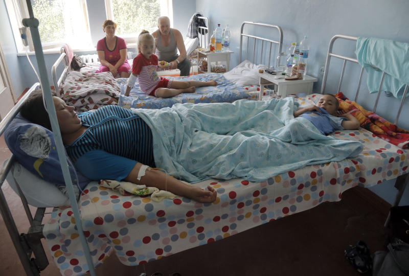 In this photo taken on Tuesday, Aug. 13, 2013, three-year old Yaroslav and his mother Lyudmila, front bed, as well as other patients lie down on their hospital beds after food poisoning in the town of Ruzhyn, Ukraine. Nearly 60 guests, including 14 children, were delivered in an ambulance from a nearby village last week, suffering from food poisoning at a wedding celebrations. They are victims of Ukraine's cult of traditional big wedding hospitality, which calls for treating guests to more food than they can eat and the hosts can safely prepare. (AP Photo/Efrem Lukatsky)