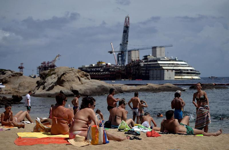 People sunbathe by the wrecked Costa Concordia cruise ship in Giglio Island on June 26, 2014 (AFP Photo/Filippo Monteforte)
