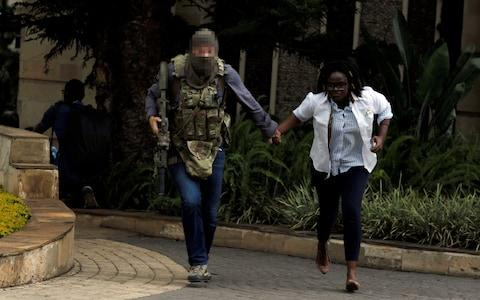A security agent evacuates an injured woman from the scene where explosions and gunshots were heard at the Dusit hotel compound, in Nairobi