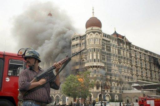 A security official stands in front of a burning section of The Taj Mahal hotel in Mumbai on November 29, 2008