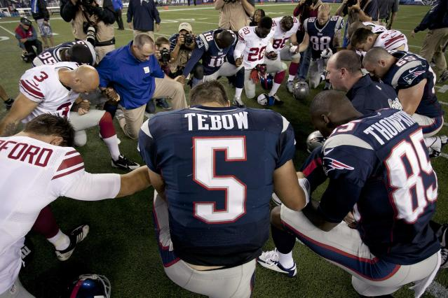 New England Patriots quarterback Tim Tebow prays with his teammates and members of the New York Giants after their NFL preseason game in Foxborough