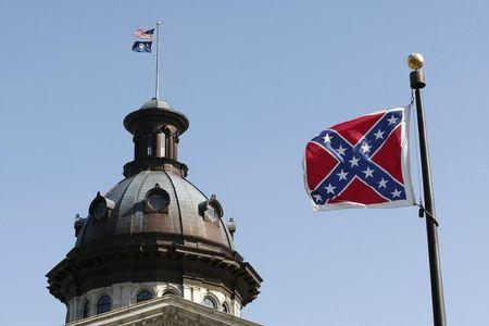 A Confederate flag flies at the base of a confederate memorial in front of the South Carolina State House in Columbia, South Carolina July 4, 2015.   REUTERS/Tami Chappell