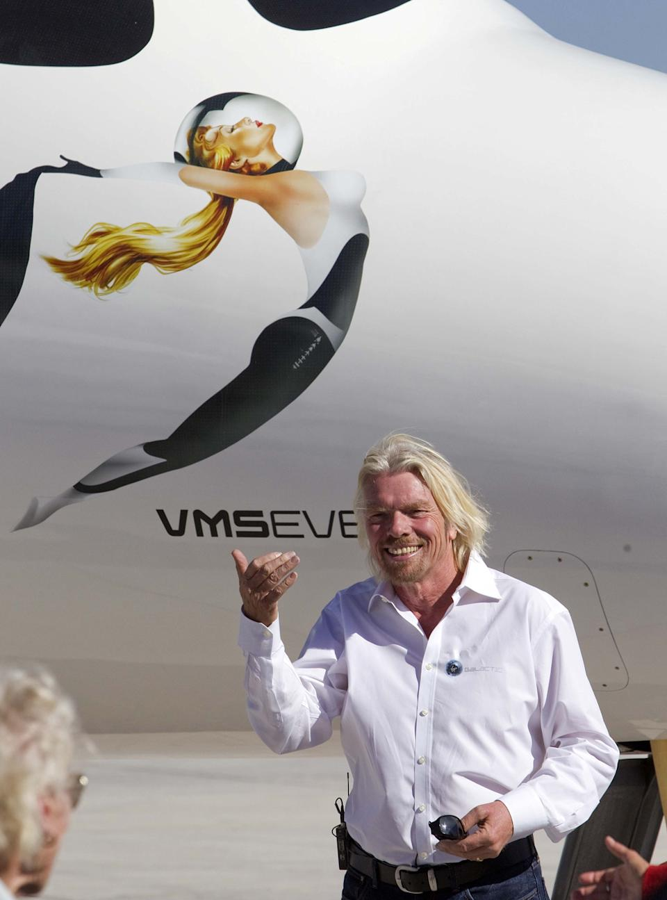 British billionaire Sir Richard Branson stands along side the spacecraft White Knight Two after a test flight outside the new Spaceport America hangar.