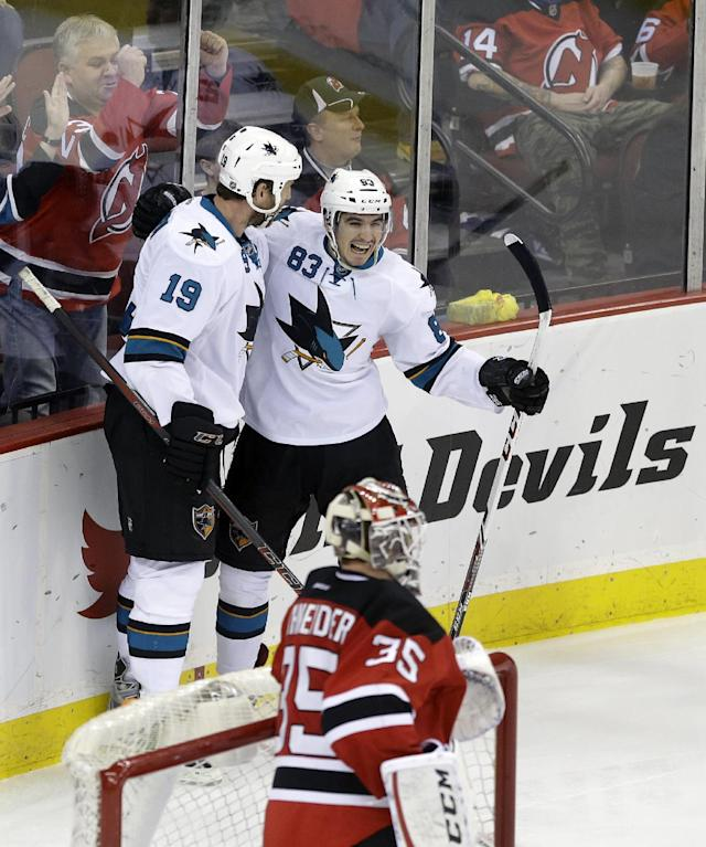 As New Jersey Devils goalie Cory Schneider (35) stands at the net, San Jose Sharks' Matt Nieto (83) celebrates his goal with teammate Joe Thornton (19) during the third period of an NHL hockey game Sunday, March. 2, 2014, in Newark, N.J. Sharks won 4-2. (AP Photo/Mel Evans)