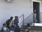 FILE - In this Aug. 15, 2018, file photo, a woman carrying a child is escorted by authorities to an apartment following the arrest of a 45-year-old Iraqi refugee, Omar Ameen in Sacramento, Calif. A federal judge in California refused Wednesday, April 21, 2021, to allow the extradition to Iraq of Ameen, accused of killing for the Islamic State, saying cellphone evidence shows he was in Turkey at the time of the slaying. The U.S. Justice Department has tried since 2018 to return Omar Abdulsattar Ameen to Iraq under a treaty with that nation. (AP Photo/Rich Pedroncelli, File)