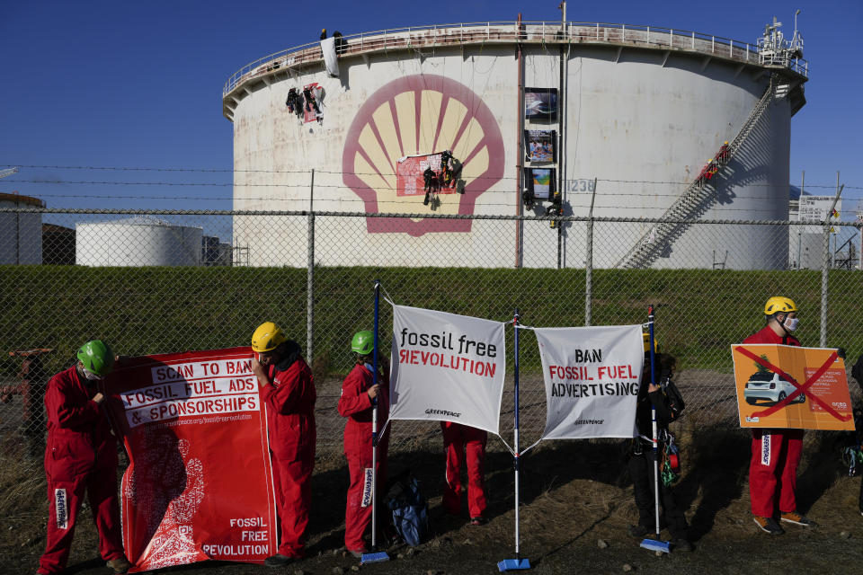 Greenpeace climate activists stage a protest at a Shell refinery in Rotterdam, Netherlands, Monday, Oct. 4, 2021. A coalition of environmental groups launched a campaign calling for a Europe-wide ban on fossil fuel advertising ahead of the United Nations Climate Change Conference, also known as COP26, which start in Glasgow on Oct. 31st, 2021. (AP Photo/Peter Dejong)