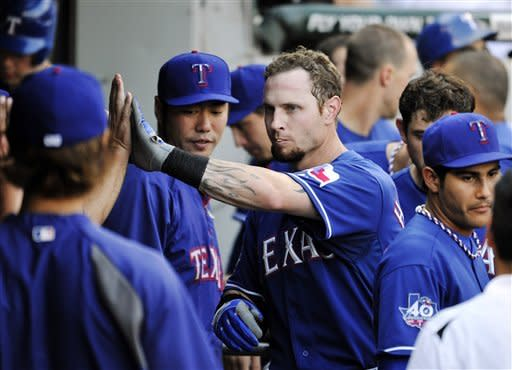 Texas Rangers' Josh Hamilton is congratulated in the dugout after hitting a solo home run during the third inning of a baseball game against the Chicago White Sox, Wednesday, July 4, 2012, in Chicago. (AP Photo/Brian Kersey)