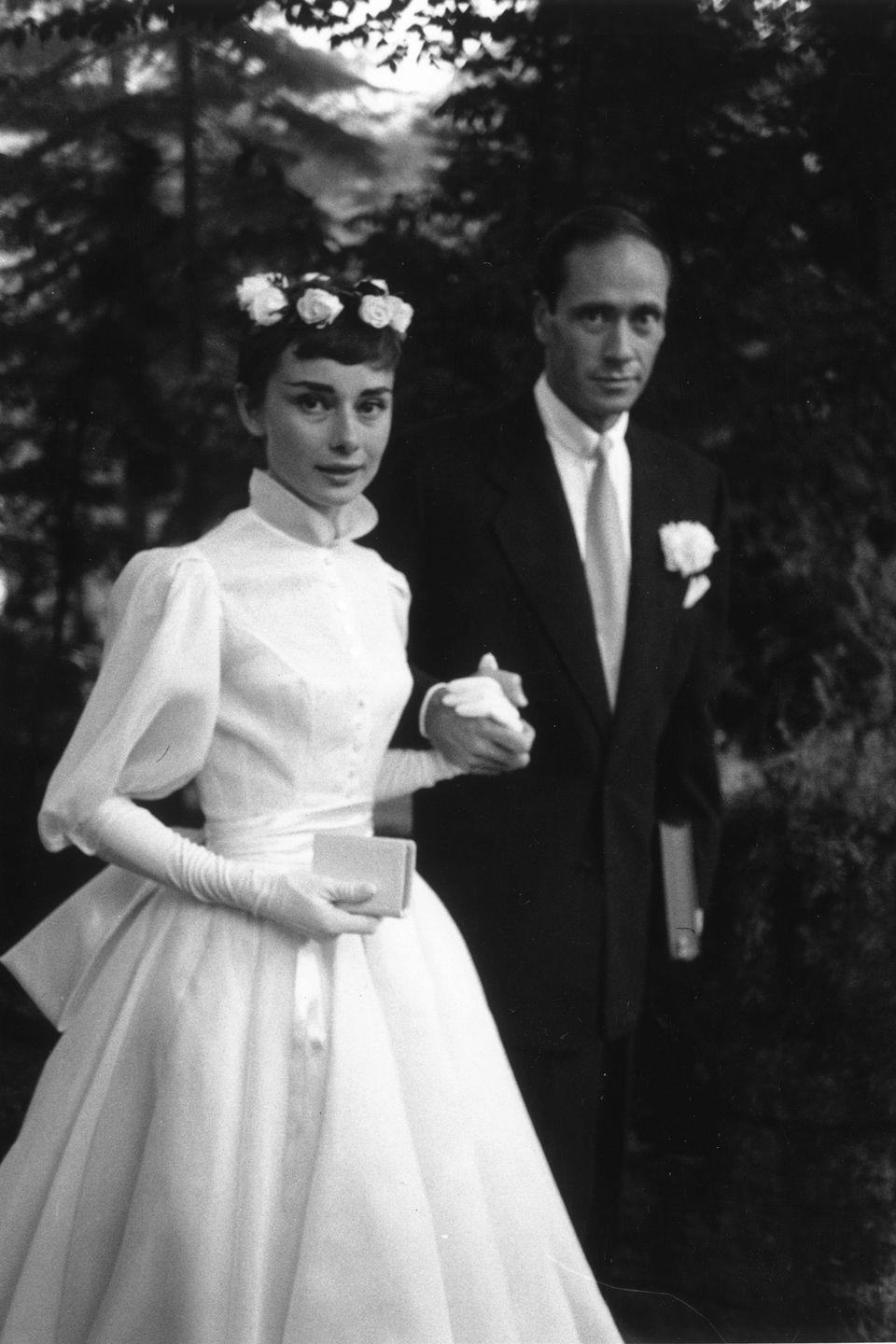 <p>Audrey Hepburn married her first husband, Mel Ferrer, in a secret wedding ceremony in Switzerland. The bride wore a high neck tea length dress with elbow length gloves and a crown of roses in her hair for the occasion. Hepburn and Ferrer had one child together and were married until 1968. </p>