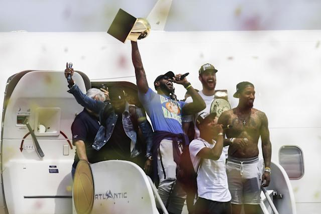 LeBron James, center, holds up the NBA championship trophy alongside teammates Kyrie Irving, left; Kevin Love, rear right; J.R. Smith, right; and Tristan Thompson, front, at the airport in Cleveland on June 20, 2016. (AP)