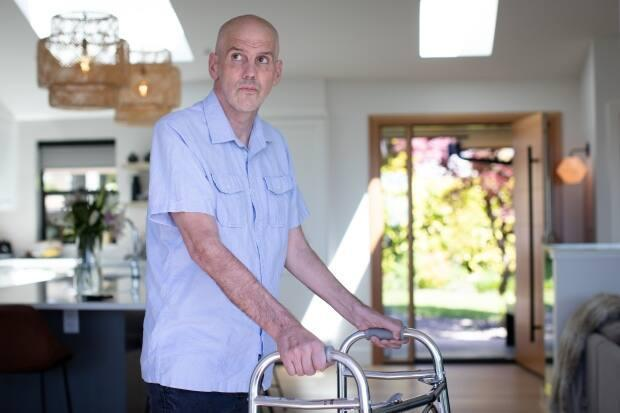 Greg Gowe was diagnosed with ALS two years ago and now uses a walker or wheelchair to move around. He's pictured in his North Vancouver home on May 14.  (Maggie MacPherson/CBC - image credit)