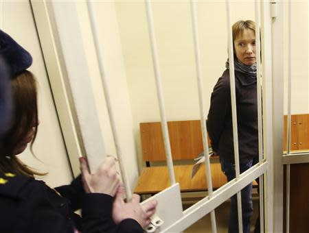 "Yekaterina Zaspa, the""Arctic Sunrise"" ship's doctor, and one of the 30 people arrested over a Greenpeace protest at the Prirazlomnaya oil rig, walks inside a defendants' cage as she attends a court session in St. Petersburg, November 18, 2013. REUTERS/Maxim Zmeyev"