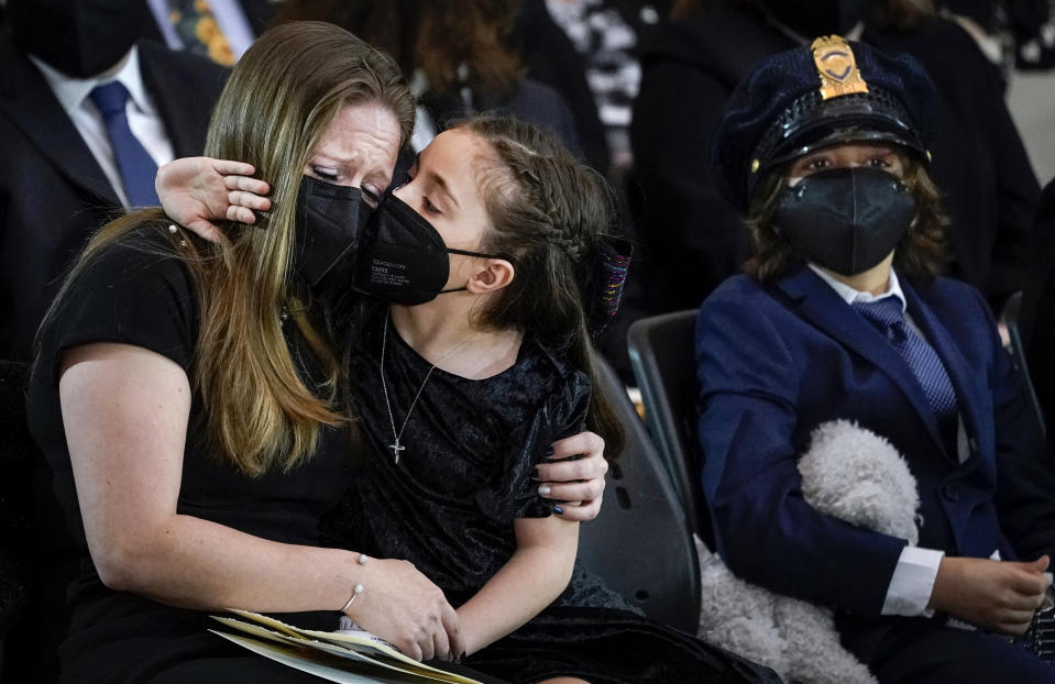 """Abigail Evans, 7, Logan Evans, 9, the children of the late U.S. Capitol Police officer William """"Billy"""" Evans, sit with their mother Shannon Terranova, left, during a memorial service as Evans lies in honor in the Rotunda at the U.S. Capitol, Tuesday, April 13, 2021 in Washington. (Drew Angerer/Pool via AP)"""