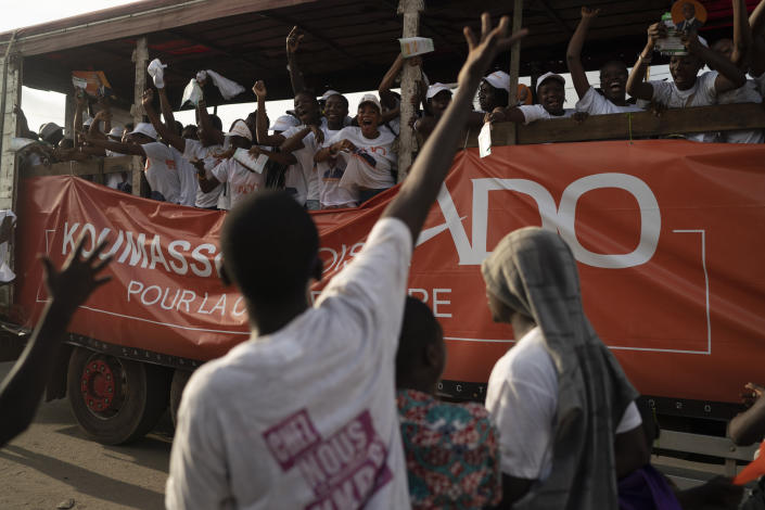 A supporter of the presidential candidate Kouadio Konan Bertin reacts as supporters of the Ivory Coast President Alassane Ouattara, ride a truck, during a final campaign rally in Abidjan, Ivory Coast, Thursday, Oct. 29, 2020. Bertin, known as KKB, has presented his candidacy as an independent candidate for the upcoming Oct. 31 election, and said he would not join the boycott proposed by two main opponents of Ivory Coast President Alassane Ouattara. (AP Photo/Leo Correa)