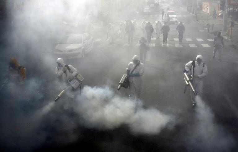 Iranian firefighters disinfect the streets of Tehran in a bid to stem the spread of the coronavirus in one of the world's worst hit countries
