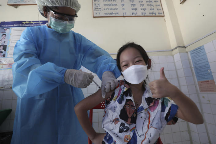 A young girl thumbs up as she receives a shot of the Sinovac's COVID-19 vaccine at a Samrong Krom health center outside Phnom Penh, Cambodia, Friday, Sept. 17, 2021. Prime Minister Hun Sen announced the start of a nationwide campaign to give COVID-19 vaccinations to children between the ages of 6 and 11 so they can return to school safely after a long absence due to measures taken against the spread of the coronavirus. (AP Photo/Heng Sinith)