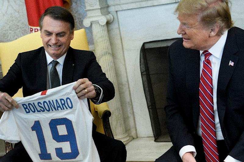 The meeting between Brazil's President Jair Bolsonaro and US President Donald Trump began with a light-hearted exchange of the US and Brazilian soccer jerseys (AFP Photo/Brendan Smialowski)