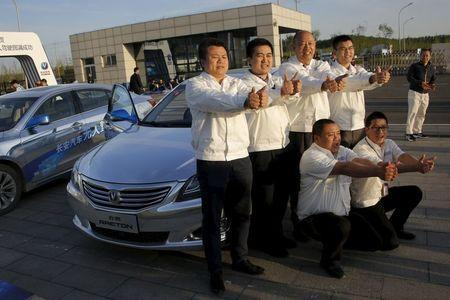 Members of Changan Automobile's self-driving car development team pose for pictures in front of their self-driving cars after the cars completed a test drive from Chongqing to Beijing, China, April 16, 2016. REUTERS/Kim Kyung-Hoon