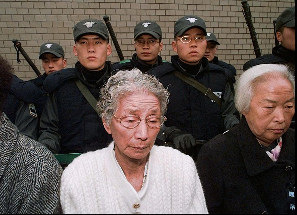"""Against a backdrop of Seoul riot policemen in front of the Japanese embassy former """"comfort women"""" bow their heads in silence as prayers are read for Kim Hak-soon Thursday, Dec. 18, 1997. Kim, who died Tuesday was the first to openly identify herself as a former sex slave of Japanese soldiers during World War II. (AP Photo/David Longstreath)"""