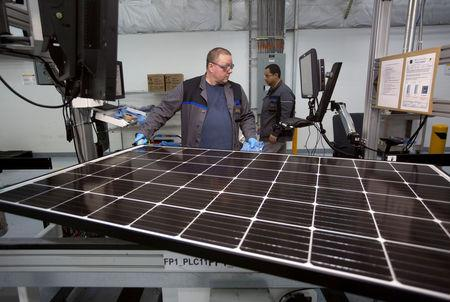 FILE PHOTO: Production operator John White checks a panel at the SolarWorld solar panel factory in Hillsboro