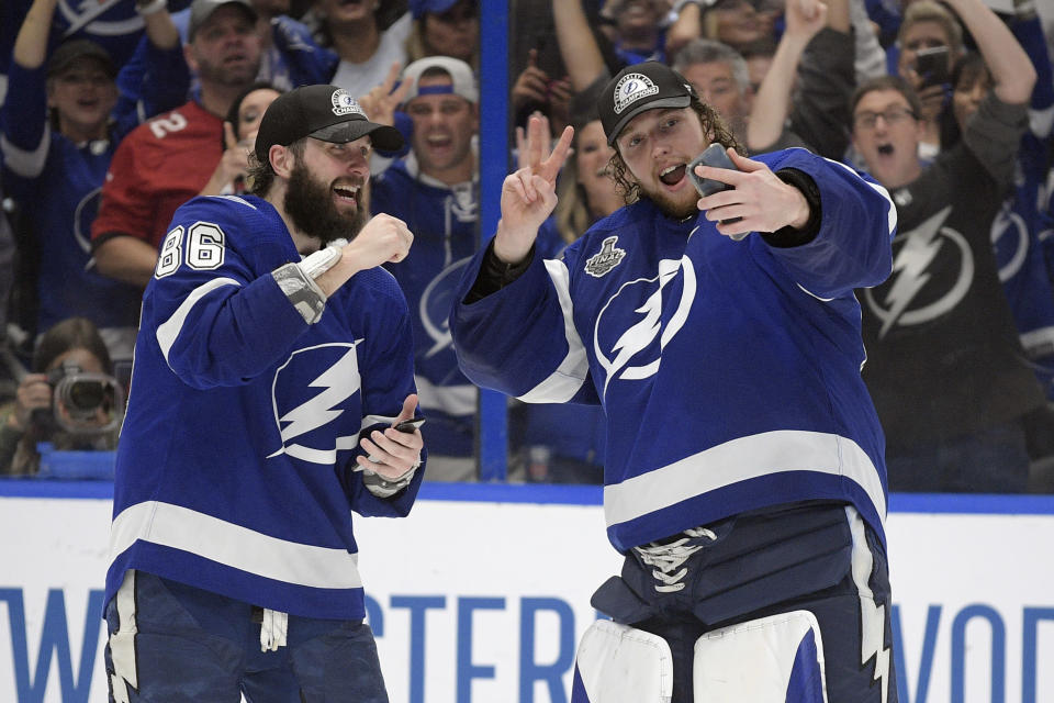 Tampa Bay Lightning right wing Nikita Kucherov (86) and goaltender Andrei Vasilevskiy (88) take selfies after the Lighting defeated the Montreal Canadiens 1-0 in Game 5 of the NHL hockey Stanley Cup finals, Wednesday, July 7, 2021, in Tampa, Fla. (AP Photo/Phelan Ebenhack)