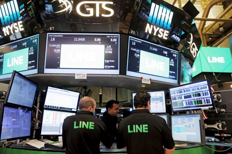 Traders look over their monitors as Japan's Line Corp. offers up its IPO on the floor of the New York Stock Exchange (NYSE) in New York City