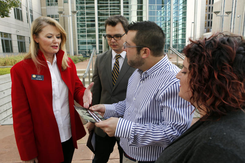 State Senator Jean White, left, shows Brian Edwards, Tom Privitere and photographer Kristina Hill, right, a brochure with an altered photograph that she took of Tom Privitere and his partner Brian Edwards outside the federal courthouse in Denver on Wednesday, Sept. 26, 2012. Privitere, Edwards and Hill filed a lawsuit in federal court on Wednesday over the fact that the photo was altered and used in a political campaign in Colorado. (AP Photo/Ed Andrieski)