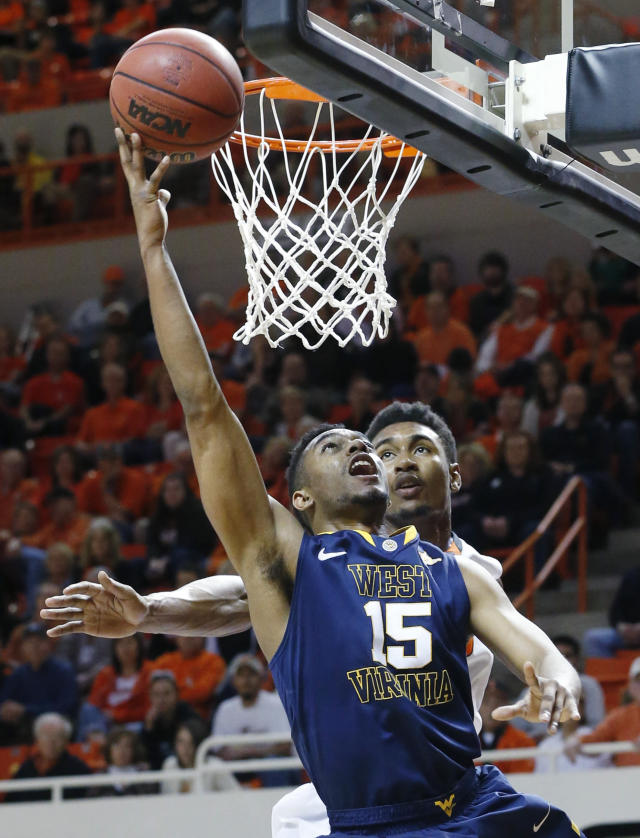West Virginia guard Terry Henderson (15) shoots in front of Oklahoma State wing Le'Bryan Nash (2) in the first half of an NCAA college basketball game in Stillwater, Okla., Saturday, Jan. 25, 2014. Oklahoma State won 81-75. (AP Photo/Sue Ogrocki)