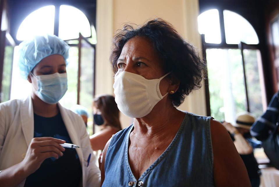 RIO DE JANIERO, BRAZIL - MAY 24: Nurse-in-training Julia Ramos vaccinates Arlete dos Santos Fonseca at a COVID-19 vaccination clinic at Museu da Republica (Museum of the Republic) on May 24, 2021 in Rio de Janeiro, Brazil. COVID-19 has now killed more than 1 million people in Latin America and the Caribbean, with nearly half of those killed in Brazil. Only three percent of the population of Latin America have been fully vaccinated against COVID-19. Health experts are warning that Brazil should brace for a new surge of COVID-19 amid a slow vaccine rollout and relaxed restrictions. The state of Sao Paulo has registered over 3 million cases of COVID-19 and more than 100,000 deaths. Nearly 450,000 people have been killed in Brazil by COVID-19, second only to the U.S. (Photo by Mario Tama/Getty Images)