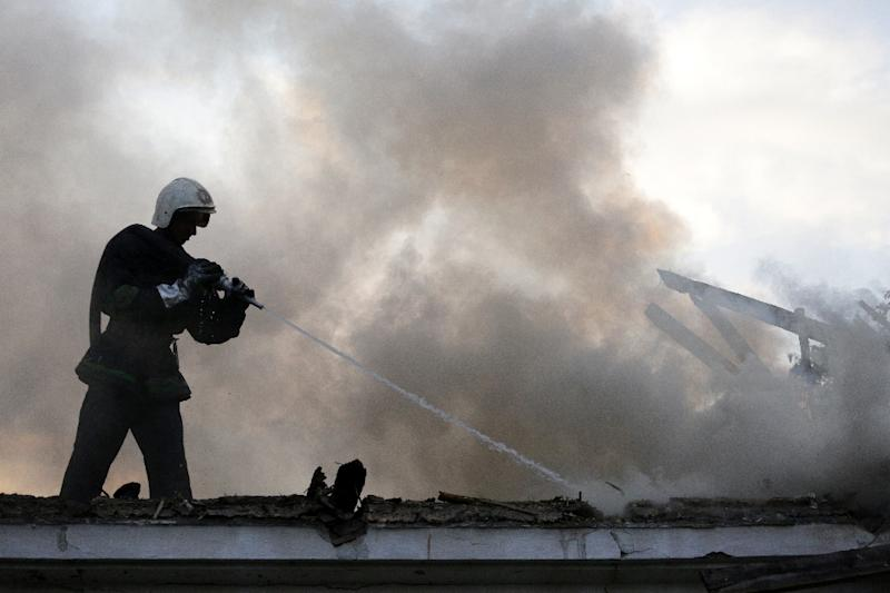 A firefighter extinguishes a house burned in shelling between Ukrainian forces and pro-Russian rebels in Oktyabrsky village, near Donetsk on August 12, 2015