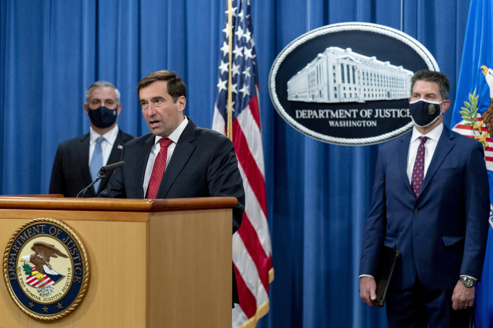 Assistant Attorney General for the National Security Division John Demers, second from left, accompanied by U.S. Attorney for the Western District of Pennsylvania Scott Brady, left, and FBI Deputy Director David Bowdich, right, speaks at a news conference at the Department of Justice, Monday, Oct. 19, 2020, in Washington. (AP Photo/Andrew Harnik, pool)