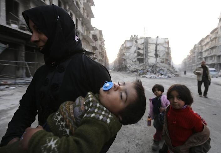 A Syrian woman and her children walk past the ruins of buildings in Aleppo on January 21, 2017 (AFP Photo/LOUAI BESHARA)