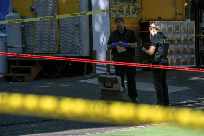 Police investigate an overnight shooting Saturday, July 17, 2021 in Portland, Ore. Police said one person died and at least six people were injured in an early morning shooting Saturday in Portland, Oregon. (Mark Graves/The Oregonian via AP)