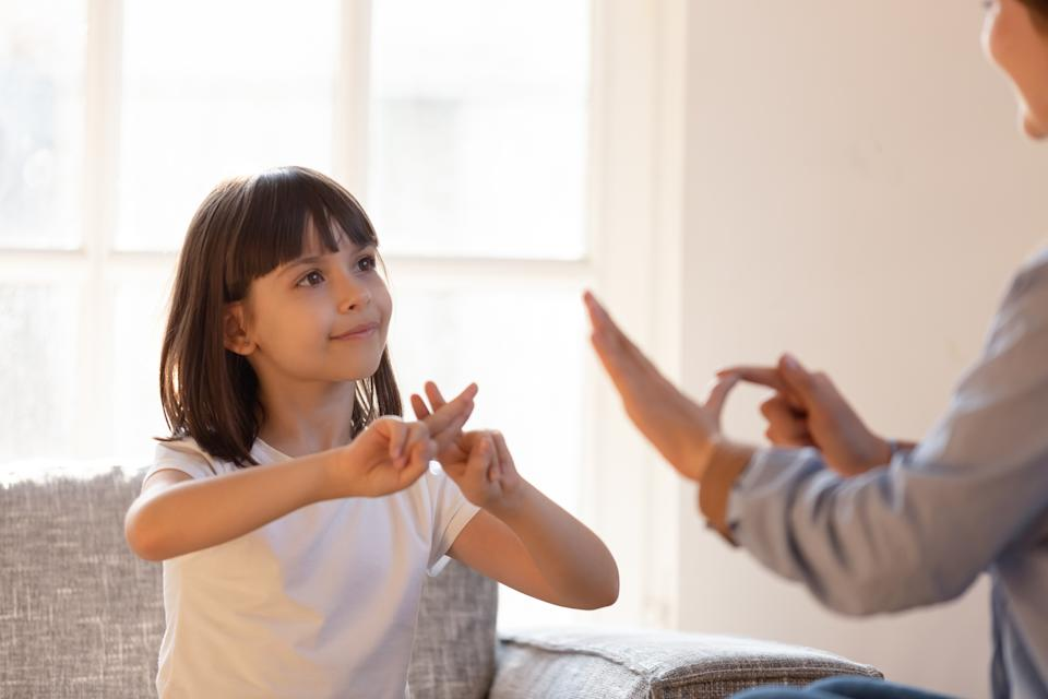 Mom communicating with deaf daughter focus on kid sitting on couch in living room make fingers shape hands talking nonverbal. Hearing loss deaf disability person sign language learning school concept