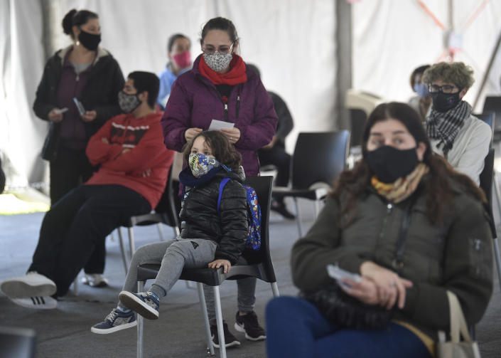 A mother stands with her son as they wait for him to get a shot of the Moderna vaccine for COVID-19, donated by the US government, at a health center in Quilmes Argentina, Tuesday, Aug. 3, 2021. Argentina is vaccinating youths with pre-existing conditions, between ages 12 and 17. (AP Photo/Gustavo Garello)