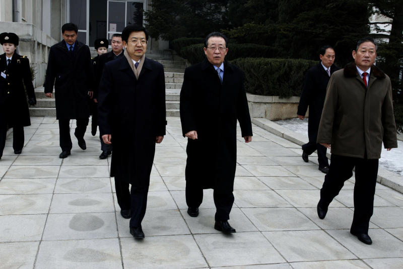 North Korea's First Vice Foreign Minister Kim Kye Gwan, center, walks out of the terminal with Guan Huabing, front left, Minister Counselor of the Chinese Embassy in Pyongyang, at Pyongyang airport in North Korea, Tuesday, Feb. 21, 2012. Kim, North Korea's top nuclear envoy, left Pyongyang for Beijing ahead of important nuclear talks with the United States later this week. (AP Photo/Kim Kwang Hyon)