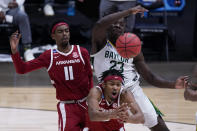 Arkansas guard Moses Moody, center, and teammate guard Jalen Tate (11) battle for a loose ball with Baylor forward Jonathan Tchamwa Tchatchoua (23) during the second half of an Elite 8 game in the NCAA men's college basketball tournament at Lucas Oil Stadium, Monday, March 29, 2021, in Indianapolis. (AP Photo/Michael Conroy)