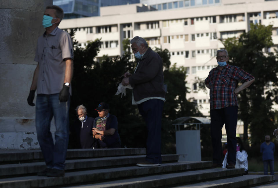 People keep social distancing while waiting in line to cast their vote in presidential election in Warsaw, Poland, Sunday, June 28, 2020. The election will test the popularity of incumbent President Andrzej Duda who is seeking a second term and of the conservative ruling party that backs him. (AP Photo/Petr David Josek)