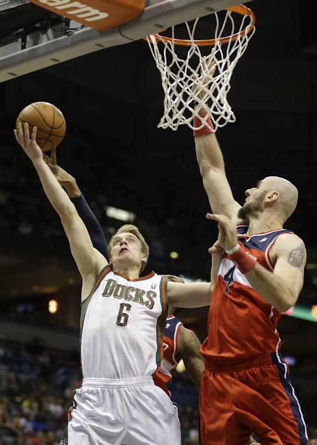 Milwaukee Bucks' Nate Wolters (6) drives against Washington Wizards' Marcin Gortat (4) during the second half of an NBA basketball game on Saturday, March 8, 2014, in Milwaukee. (AP Photo/Jeffrey Phelps)