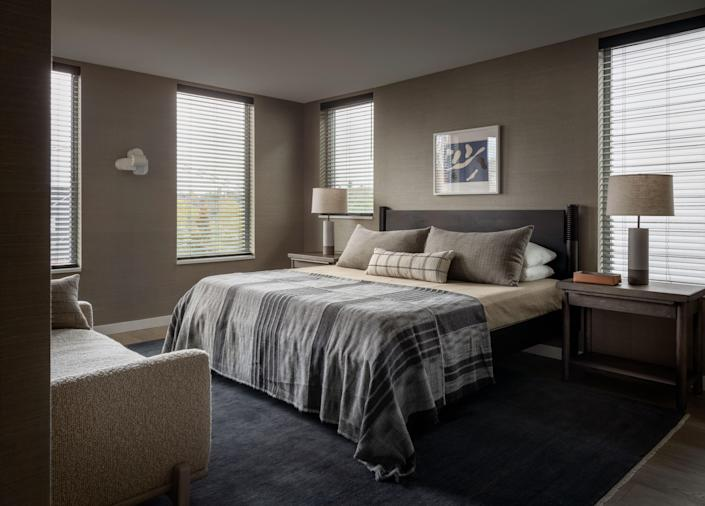 Paquette covered the walls of the primary bedroom with grass cloth. Hanging above the bed is a piece by Jean Arp that Paquette and his husband bought in Paris. Opposite the bed is the George daybed from Paquette's own furniture collection, named after one of his dachshunds.