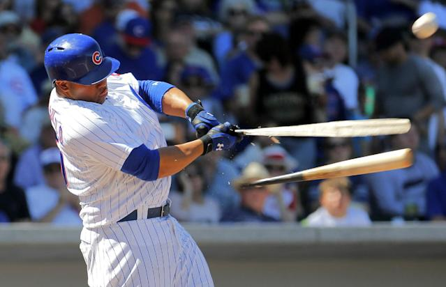 Chicago Cubs' Welington Castillo breaks his bat as he flies out against the Cincinnati Reds during the first inning of an exhibition spring training baseball game, Saturday, March 22, 2014, in Mesa, Ariz. (AP Photo/Matt York)